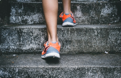 Woman walking up the stairs with tennis shoes