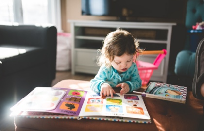 Baby reading a children's book in the living room