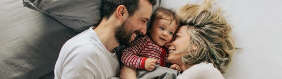 Parents lying in bed with their son