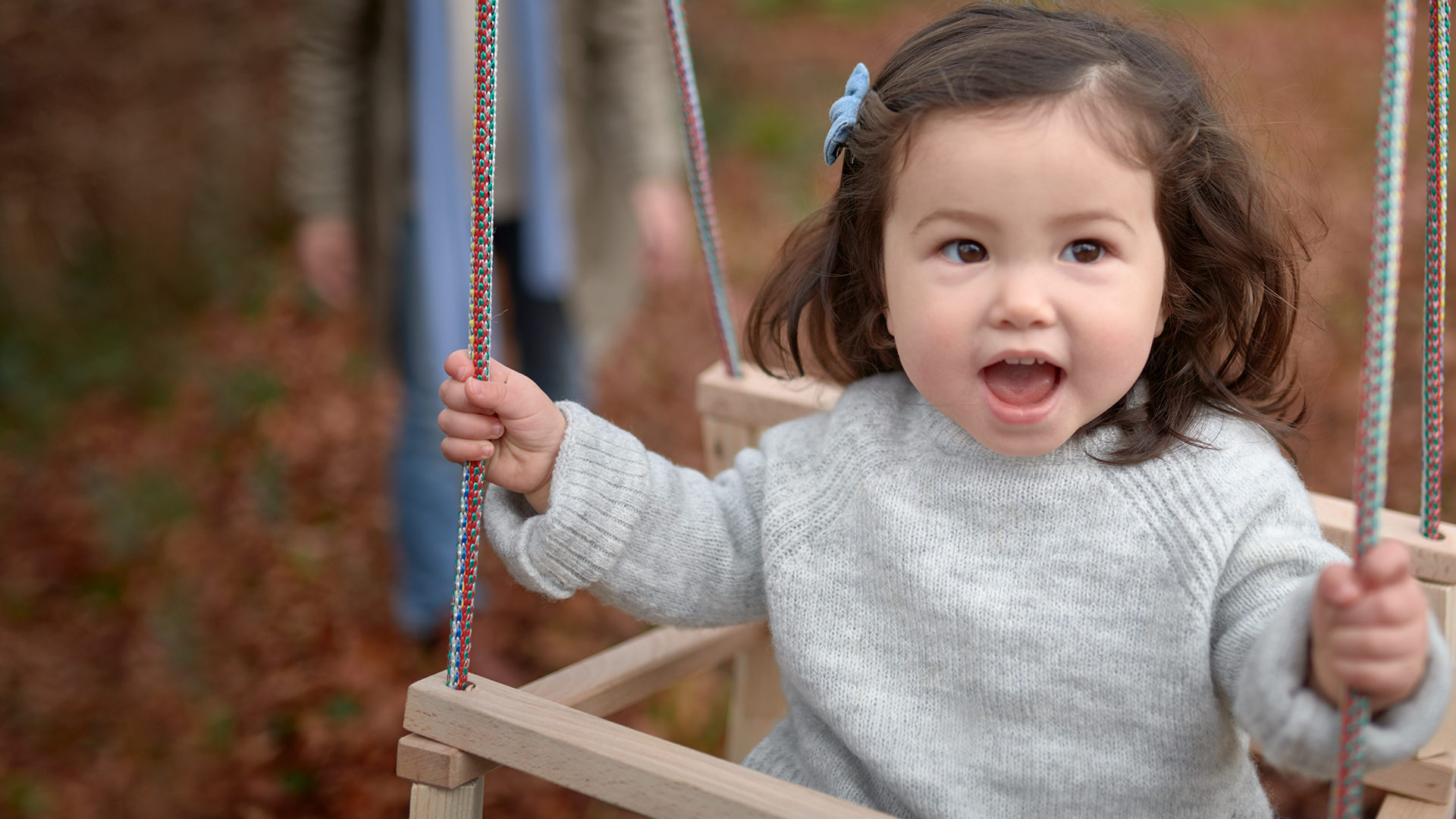 Toddler smiling on a swing