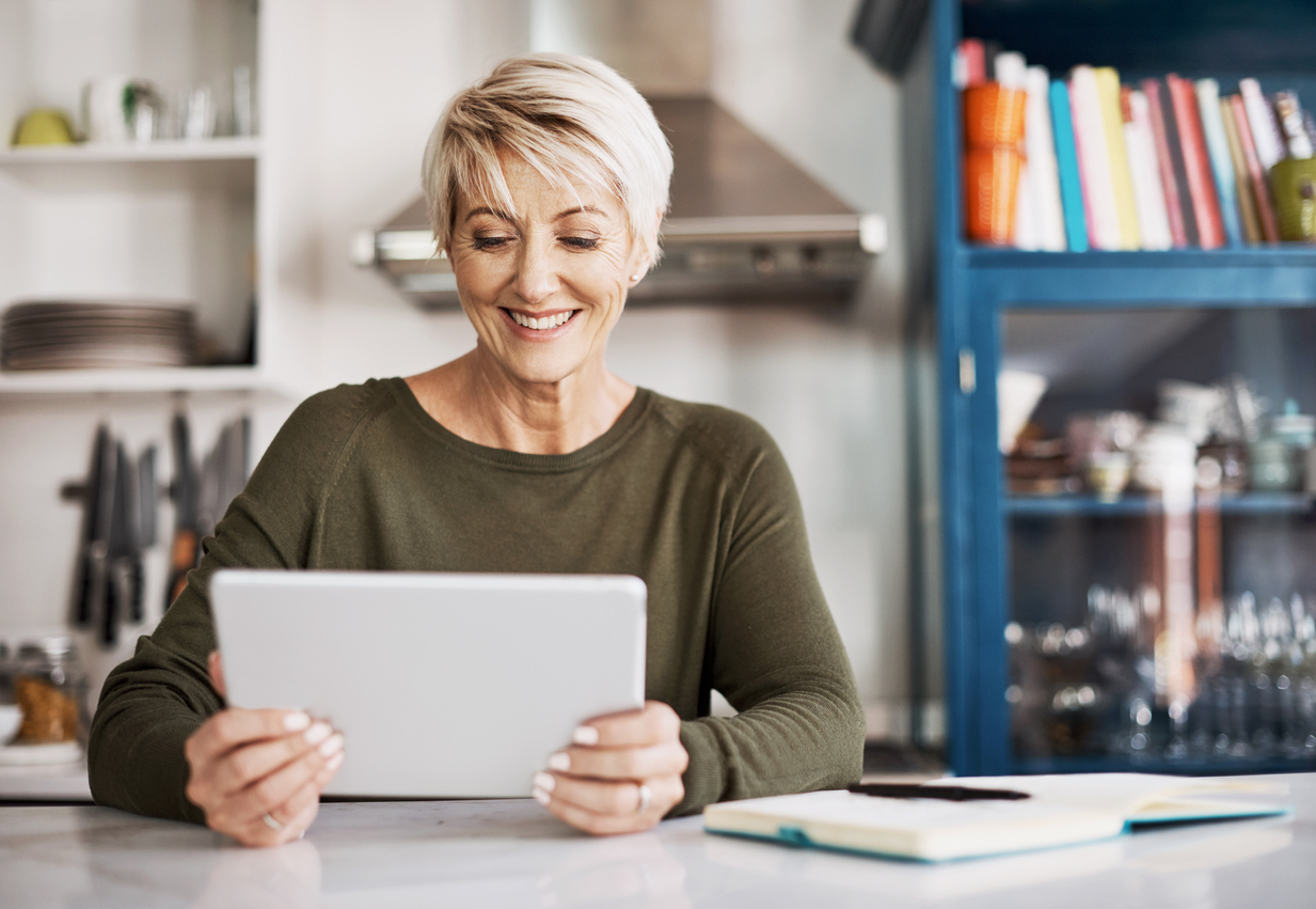 Mature woman using a digital tablet at home