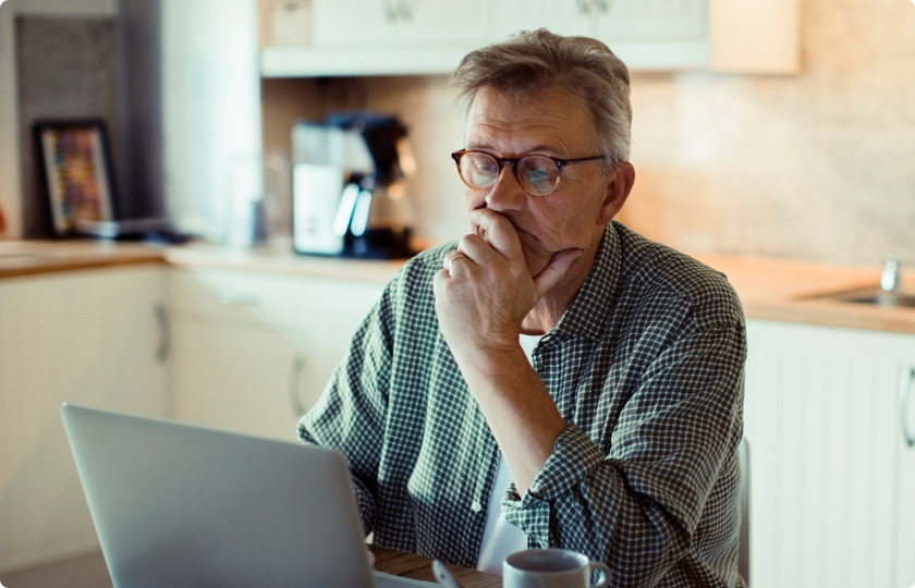 Older man sitting and working on his laptop