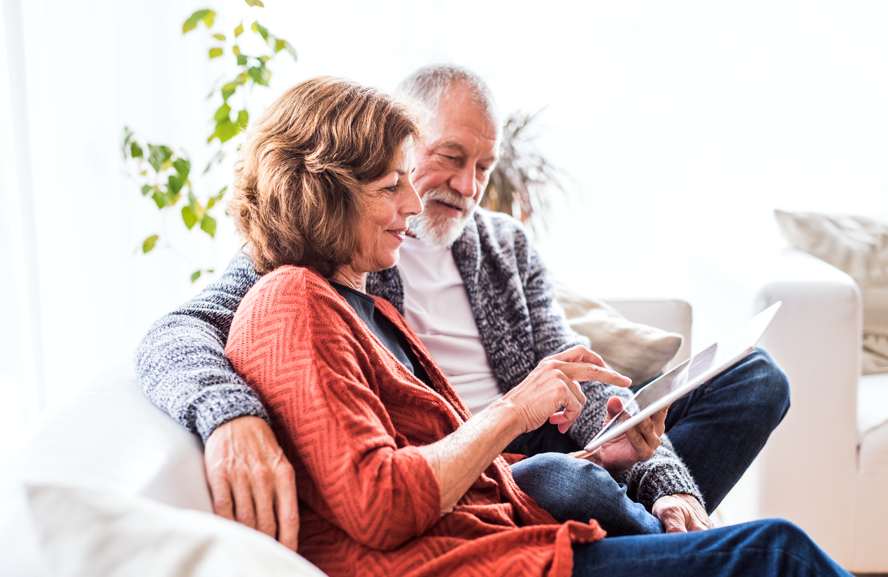 Happy senior couple with tablet relaxing at home.