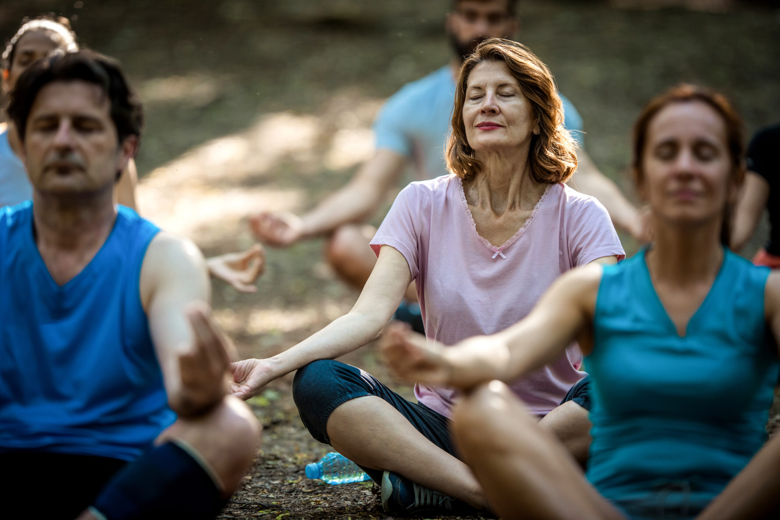 Group of athletic people in Lotus position meditating on exercise class in nature.