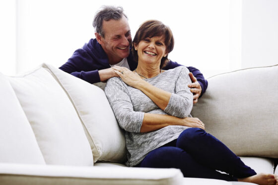 Mature couple holding hands and laughing on the couch