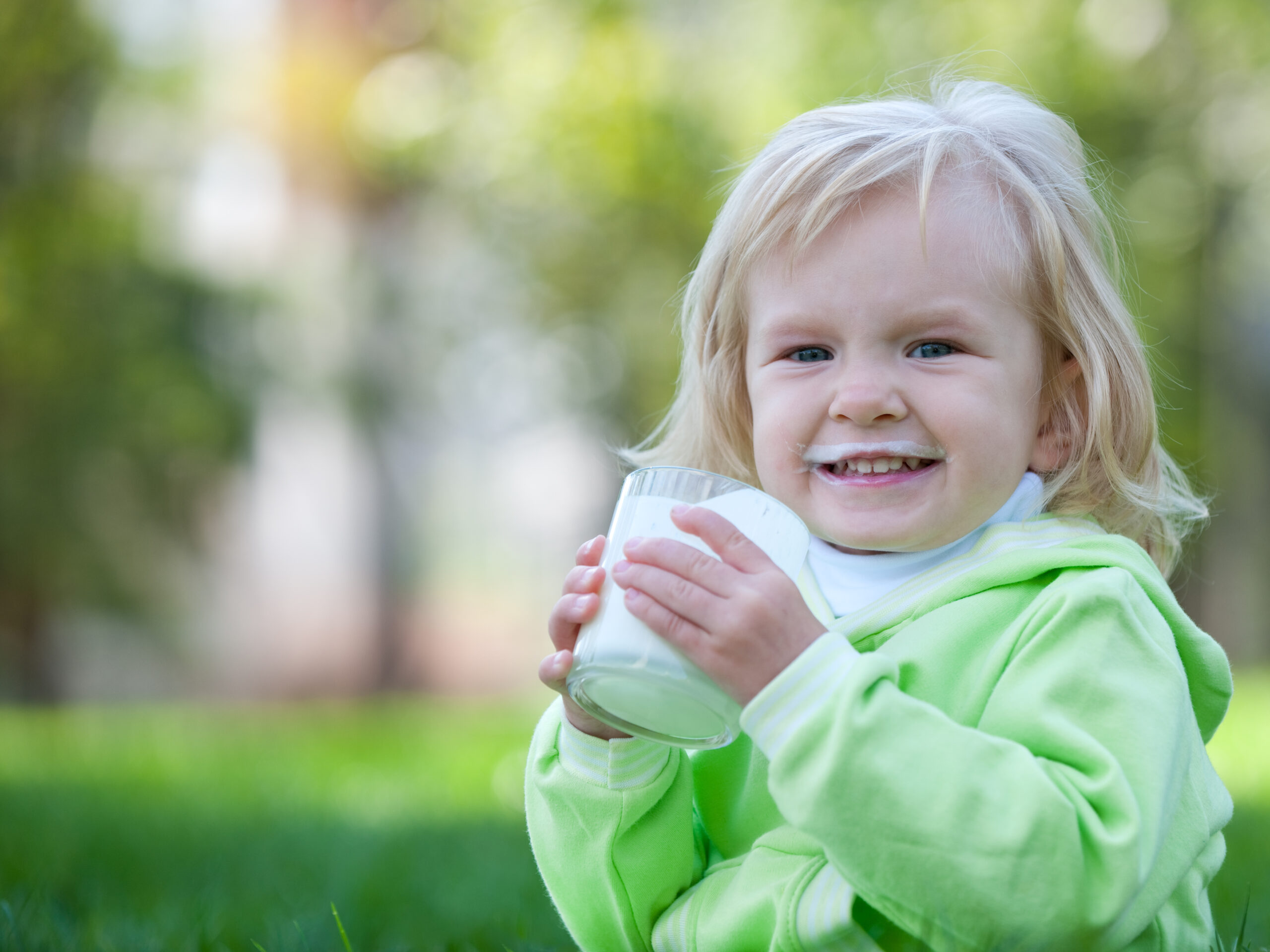 Blonde toddler drinking a glass of milk in the garden outdoors